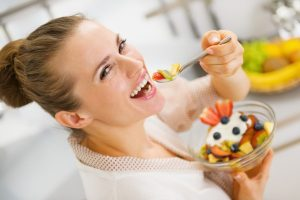 Happy Young Housewife Eating Fruits Salad
