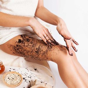 woman-applying-body-scrub-to-leg