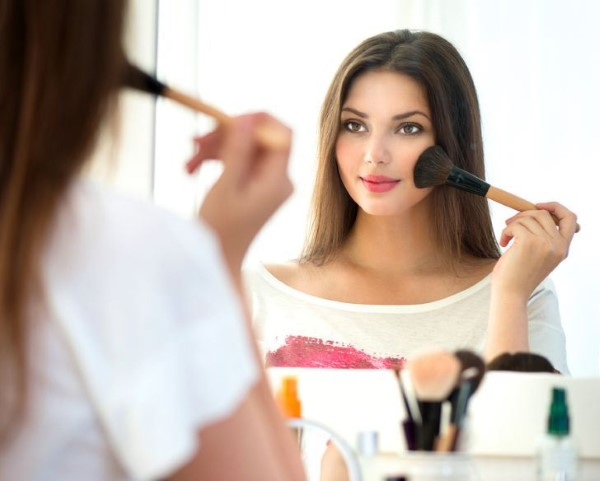 Beauty woman applying makeup. Beautiful girl looking in the mirr